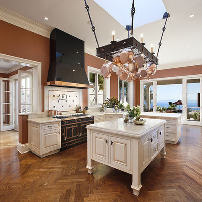 Kitchen - large mediterranean medium tone wood floor kitchen idea in Santa Barbara with raised-panel cabinets, marble countertops, white cabinets, black appliances and an island