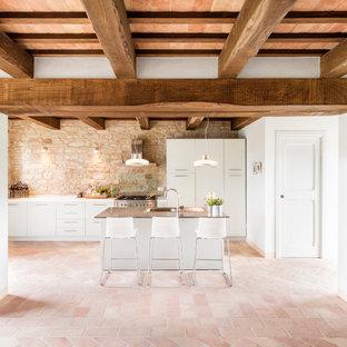 Новые идеи обустройства дома: большая параллельная кухня-гостиная в стиле модернизм с плоскими фасадами, белыми фасадами, полом из терракотовой плитки, островом, двойной раковиной и техникой из нержавеющей стали
