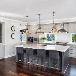 Inspiration for a beach style kitchen in Brisbane with a double-bowl sink, shaker cabinets, grey cabinets, white splashback, stainless steel appliances, dark hardwood floors, with island, brown floor and white benchtop.