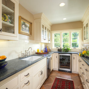 Mid-sized traditional kitchen pantry ideas - Example of a mid-sized classic u-shaped porcelain tile kitchen pantry design in Sacramento with no island, recessed-panel cabinets, white cabinets, soapstone countertops, white backsplash, ceramic backsplash, stainless steel appliances and a single-bowl sink