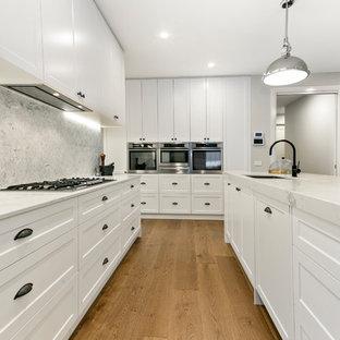 メルボルンの大きいトランジショナルスタイルのおしゃれなキッチン (アンダーカウンターシンク、シェーカースタイル扉のキャビネット、白いキャビネット、クオーツストーンカウンター、グレーのキッチンパネル、大理石の床、白い調理設備、リノリウムの床、茶色い床) の写真