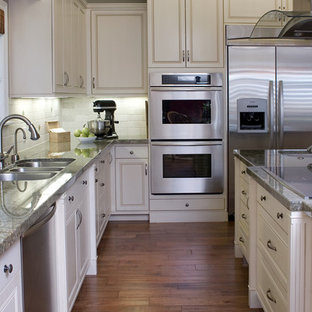Photo of a traditional kitchen in Los Angeles with stainless steel appliances, a triple-bowl sink, raised-panel cabinets, white cabinets, white splashback and granite benchtops.