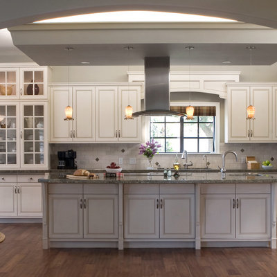 Inspiration for a timeless kitchen remodel in Los Angeles with glass-front cabinets, stainless steel appliances, white cabinets, white backsplash and granite countertops