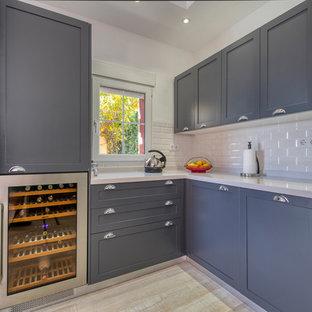 アリカンテの大きいシャビーシック調のおしゃれなキッチン (アンダーカウンターシンク、シェーカースタイル扉のキャビネット、グレーのキャビネット、人工大理石カウンター、白いキッチンパネル、サブウェイタイルのキッチンパネル、パネルと同色の調理設備、塗装フローリング、アイランドなし、グレーの床、白いキッチンカウンター) の写真