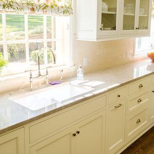 ポートランドの中くらいのトラディショナルスタイルのおしゃれなキッチン (ダブルシンク、シェーカースタイル扉のキャビネット、白いキャビネット、人工大理石カウンター、ベージュキッチンパネル、磁器タイルのキッチンパネル、白い調理設備、濃色無垢フローリング) の写真