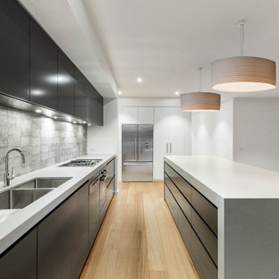 Inspiration for a modern l-shaped kitchen in Melbourne with an undermount sink, flat-panel cabinets, black cabinets, grey splashback, stainless steel appliances, light hardwood floors, with island, beige floor and white benchtop.