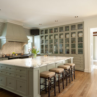 Mid-sized traditional u-shaped separate kitchen in Dallas with glass-front cabinets, subway tile splashback, green cabinets, a farmhouse sink, marble benchtops, grey splashback, medium hardwood floors and with island.