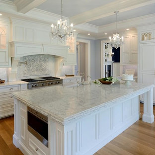 Photo of a large shabby-chic style l-shaped separate kitchen in Boston with a farmhouse sink, beaded inset cabinets, white cabinets, marble benchtops, grey splashback, mosaic tile splashback, panelled appliances, light hardwood floors, with island and brown floor.