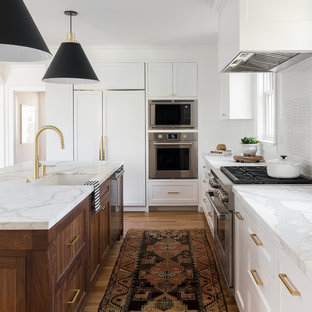 Transitional kitchen appliance - Transitional l-shaped light wood floor kitchen photo in Seattle with an undermount sink, shaker cabinets, white cabinets, white backsplash, matchstick tile backsplash, stainless steel appliances, an island and white countertops