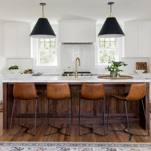 Transitional kitchen pictures - Transitional l-shaped medium tone wood floor and brown floor kitchen photo in Portland with an undermount sink, recessed-panel cabinets, white cabinets, white backsplash, stainless steel appliances, an island and white countertops