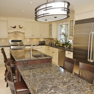 Mid-sized traditional l-shaped separate kitchen in Toronto with an undermount sink, recessed-panel cabinets, yellow cabinets, quartz benchtops, beige splashback, stone tile splashback, stainless steel appliances, porcelain floors and with island.