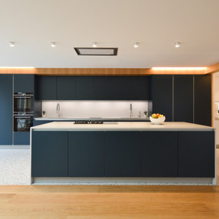 Photo of a large contemporary galley open plan kitchen in London with a built-in sink, flat-panel cabinets, blue cabinets, quartz worktops, grey splashback, stone slab splashback, stainless steel appliances, ceramic flooring, an island and grey worktops.