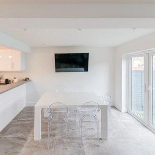 ロンドンの中くらいのコンテンポラリースタイルのおしゃれなキッチン (ドロップインシンク、フラットパネル扉のキャビネット、白いキャビネット、ラミネートカウンター、白いキッチンパネル、レンガのキッチンパネル、シルバーの調理設備、セメントタイルの床、マルチカラーの床、グレーのキッチンカウンター) の写真