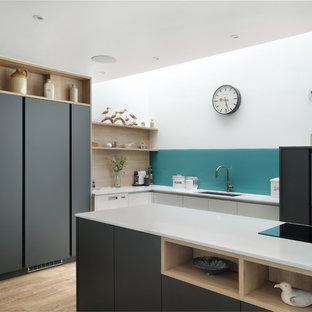 This is an example of a medium sized contemporary l-shaped kitchen/diner in Gloucestershire with flat-panel cabinets, grey cabinets, quartz worktops, blue splashback, glass sheet splashback, black appliances, medium hardwood flooring, white worktops, a submerged sink and a breakfast bar.