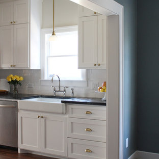 This is an example of a mid-sized arts and crafts galley eat-in kitchen in Houston with a farmhouse sink, shaker cabinets, white cabinets, soapstone benchtops, white splashback, ceramic splashback, stainless steel appliances, medium hardwood floors and a peninsula.