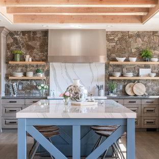 Große Rustikale Küche in U-Form mit Küchengeräten aus Edelstahl, hellem Holzboden, Kücheninsel, profilierten Schrankfronten, braunen Schränken, Küchenrückwand in Blau und grauer Arbeitsplatte in Sonstige