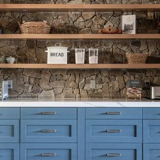 Idées déco pour une grand cuisine américaine montagne en U avec un placard à porte plane, des portes de placard en bois brun, un électroménager en acier inoxydable, un sol en bois clair et un îlot central.