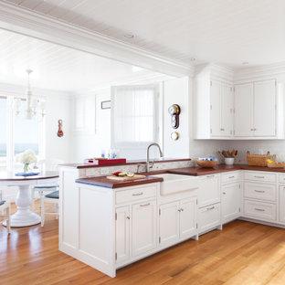 Idéer för ett maritimt brun kök, med en rustik diskho, luckor med profilerade fronter, vita skåp, träbänkskiva, vitt stänkskydd, mellanmörkt trägolv, en halv köksö och brunt golv