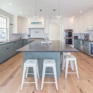ポートランド(メイン)のビーチスタイルのおしゃれなアイランドキッチン (アンダーカウンターシンク、シェーカースタイル扉のキャビネット、青いキャビネット、白いキッチンパネル、シルバーの調理設備の、淡色無垢フローリング、ベージュの床、グレーのキッチンカウンター、御影石カウンター) の写真