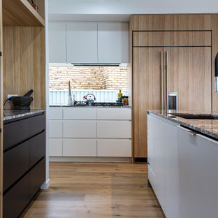Photo of a contemporary u-shaped kitchen in Sunshine Coast with an undermount sink, flat-panel cabinets, white cabinets, window splashback, panelled appliances, medium hardwood floors, with island, brown floor and grey benchtop.