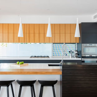 Photo of a contemporary galley open plan kitchen in Brisbane with an undermount sink, flat-panel cabinets, light wood cabinets, glass sheet splashback, stainless steel appliances, light hardwood floors and with island.
