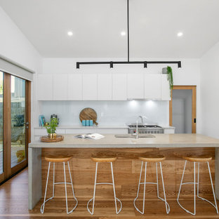 Mid-sized contemporary galley open plan kitchen in Melbourne with an undermount sink, flat-panel cabinets, white cabinets, concrete benchtops, white splashback, glass sheet splashback, stainless steel appliances, medium hardwood floors, with island, beige floor, grey benchtop and vaulted.