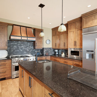 Design ideas for an expansive country u-shaped kitchen in Vancouver with a double-bowl sink, beaded inset cabinets, medium wood cabinets, granite benchtops, grey splashback, slate splashback, stainless steel appliances, light hardwood floors, with island and black benchtop.