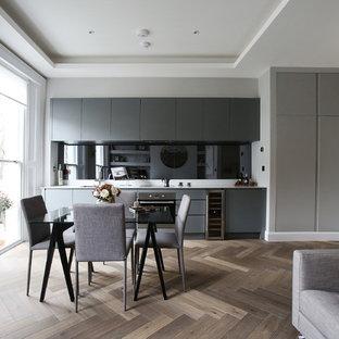 Offene, Einzeilige Moderne Küche ohne Insel mit Unterbauwaschbecken, flächenbündigen Schrankfronten, grauen Schränken, Küchenrückwand in Schwarz und hellem Holzboden in London