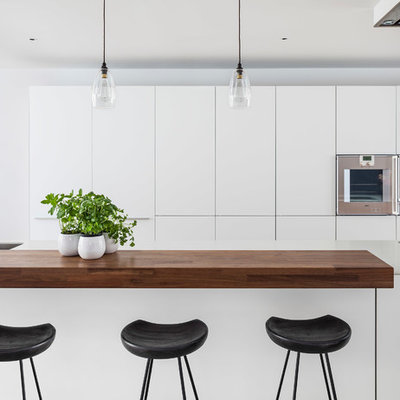 Kitchen - modern single-wall kitchen idea in London with flat-panel cabinets, white cabinets, an island, an undermount sink, solid surface countertops and stainless steel appliances