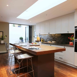 This is an example of a medium sized contemporary single-wall kitchen in London with recessed-panel cabinets, medium hardwood flooring, an island and brown floors.
