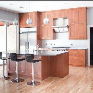 Réalisation d'une grand cuisine américaine linéaire minimaliste avec un électroménager en acier inoxydable, un évier 2 bacs, un placard à porte shaker, des portes de placard en bois brun, un plan de travail en zinc, une crédence blanche, un sol en bois brun, un îlot central et un sol marron.