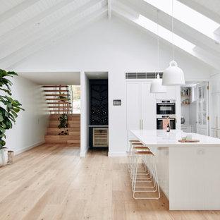 Maritim inredning av ett stort vit vitt kök, med en undermonterad diskho, skåp i shakerstil, vita skåp, bänkskiva i kvarts, vitt stänkskydd, rostfria vitvaror, ljust trägolv, en köksö och beiget golv