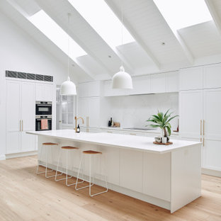 Design ideas for a large contemporary galley open plan kitchen in Melbourne with an undermount sink, shaker cabinets, white cabinets, quartz benchtops, white splashback, stainless steel appliances, light hardwood floors, with island, beige floor, white benchtop and recessed.