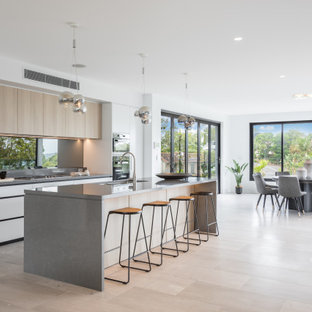 Contemporary galley kitchen in Sydney with an undermount sink, flat-panel cabinets, white cabinets, light hardwood floors, with island, beige floor and grey benchtop.