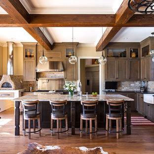 Diseño de cocina rústica con fregadero sobremueble, puertas de armario de madera oscura, encimera de granito, salpicadero multicolor, salpicadero de azulejos de piedra, electrodomésticos de acero inoxidable, suelo de madera en tonos medios, una isla, suelo marrón y encimeras negras