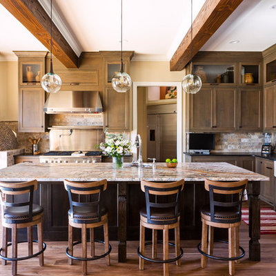 Inspiration for a rustic l-shaped medium tone wood floor and brown floor kitchen remodel in Charlotte with a farmhouse sink, granite countertops, multicolored backsplash, stone tile backsplash, stainless steel appliances, an island, black countertops, shaker cabinets and dark wood cabinets