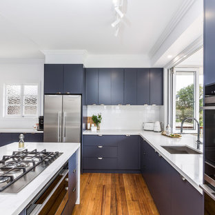 Inspiration for a small transitional l-shaped eat-in kitchen in Brisbane with an undermount sink, flat-panel cabinets, blue cabinets, quartz benchtops, white splashback, subway tile splashback, black appliances, medium hardwood floors, with island, brown floor and white benchtop.