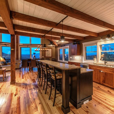 Eat-in kitchen - large rustic l-shaped light wood floor and brown floor eat-in kitchen idea in Portland Maine with an undermount sink, flat-panel cabinets, medium tone wood cabinets, granite countertops, stainless steel appliances and an island