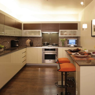 Design ideas for a large asian u-shaped eat-in kitchen in Kansas City with a double-bowl sink, raised-panel cabinets, white cabinets, solid surface benchtops, multi-coloured splashback, mosaic tile splashback, stainless steel appliances, dark hardwood floors, with island and brown floor.