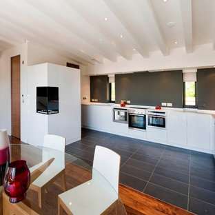Example of a minimalist l-shaped eat-in kitchen design in London with a drop-in sink, flat-panel cabinets, white cabinets and stainless steel appliances