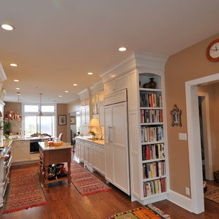 Kitchen - large traditional medium tone wood floor and brown floor kitchen idea in New York with an undermount sink, shaker cabinets, white cabinets, paneled appliances and an island