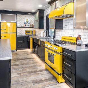 Große Industrial Wohnküche mit Glasfronten, schwarzen Schränken, Edelstahl-Arbeitsplatte, Küchenrückwand in Weiß, Rückwand aus Metrofliesen, bunten Elektrogeräten, Laminat, Kücheninsel und beigem Boden in Sonstige