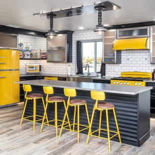 Bild på ett stort industriellt grå grått kök, med luckor med glaspanel, svarta skåp, bänkskiva i rostfritt stål, vitt stänkskydd, stänkskydd i tunnelbanekakel, färgglada vitvaror, laminatgolv, en köksö, beiget golv och en rustik diskho