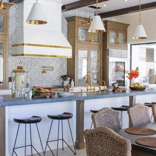 サンディエゴのビーチスタイルのおしゃれなキッチン (ガラス扉のキャビネット、中間色木目調キャビネット、グレーのキッチンカウンター) の写真