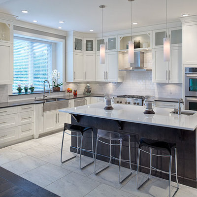 Example of a large transitional l-shaped ceramic tile eat-in kitchen design in Vancouver with a double-bowl sink, shaker cabinets, white cabinets, solid surface countertops, white backsplash, ceramic backsplash, stainless steel appliances and an island