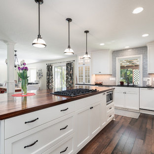 Mid-sized country l-shaped eat-in kitchen in Portland with an integrated sink, flat-panel cabinets, white cabinets, wood benchtops, grey splashback, subway tile splashback, stainless steel appliances, dark hardwood floors and with island.