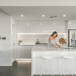Contemporary open plan kitchen in Perth with a double-bowl sink, flat-panel cabinets, white cabinets, white splashback, stainless steel appliances, with island, brown floor and white benchtop.