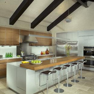 Foto på ett funkis kök, med rostfria vitvaror och träbänkskiva