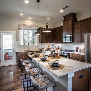 アトランタの中くらいのインダストリアルスタイルのおしゃれなキッチン (アンダーカウンターシンク、シェーカースタイル扉のキャビネット、中間色木目調キャビネット、クオーツストーンカウンター、白いキッチンパネル、サブウェイタイルのキッチンパネル、シルバーの調理設備、無垢フローリング、マルチカラーの床、白いキッチンカウンター) の写真