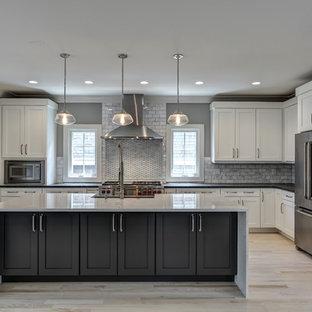 Modern inredning av ett stort l-kök, med en rustik diskho, skåp i shakerstil, vita skåp, bänkskiva i täljsten, grått stänkskydd, stänkskydd i stenkakel, rostfria vitvaror, ljust trägolv och en köksö